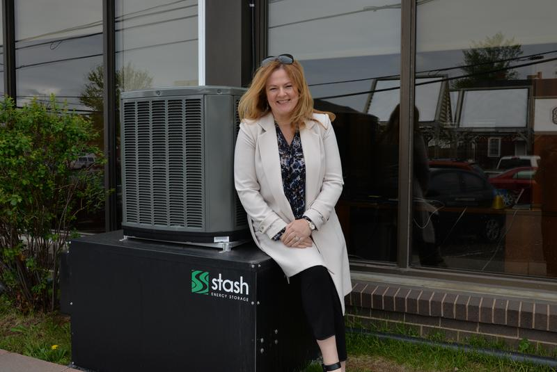 Kim Griffin, manager of customer service, corporate communications and public affairs with Maritime Electric, poses with the Stash unit installed on the building in Charlottetown.